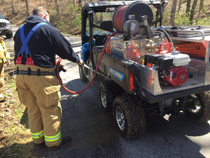 Firefighters cleaning off the ATV before returning home