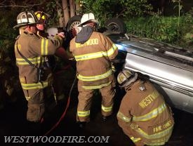 Firefighters work to extricate a patient from an overturned car that landed in a creek.