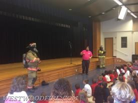 Firefighter/EMT Crawford discusses to the children about firefighter turnout gear.