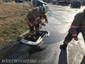 Sadsburyville firefighters control the spill from entering a storm drain.