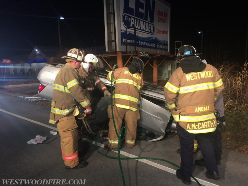Firefighters use hydraulic rescue tools to open a car's side to free the occupant.
