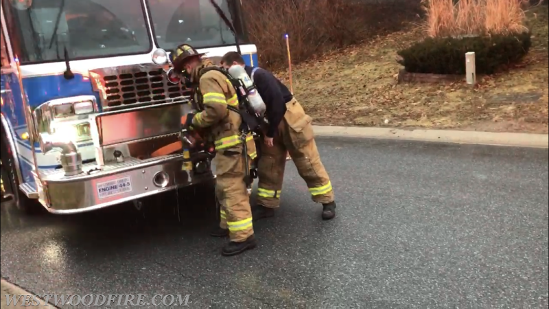 Firefighters deploy a hose line from the front bumper