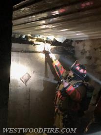 Firefighters work in the sub-basement under the fire to open up for hot spots.
