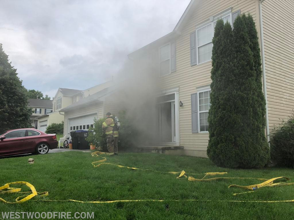 Westwood firefighters stretch a hose line from Engine 44-5 to the front door.