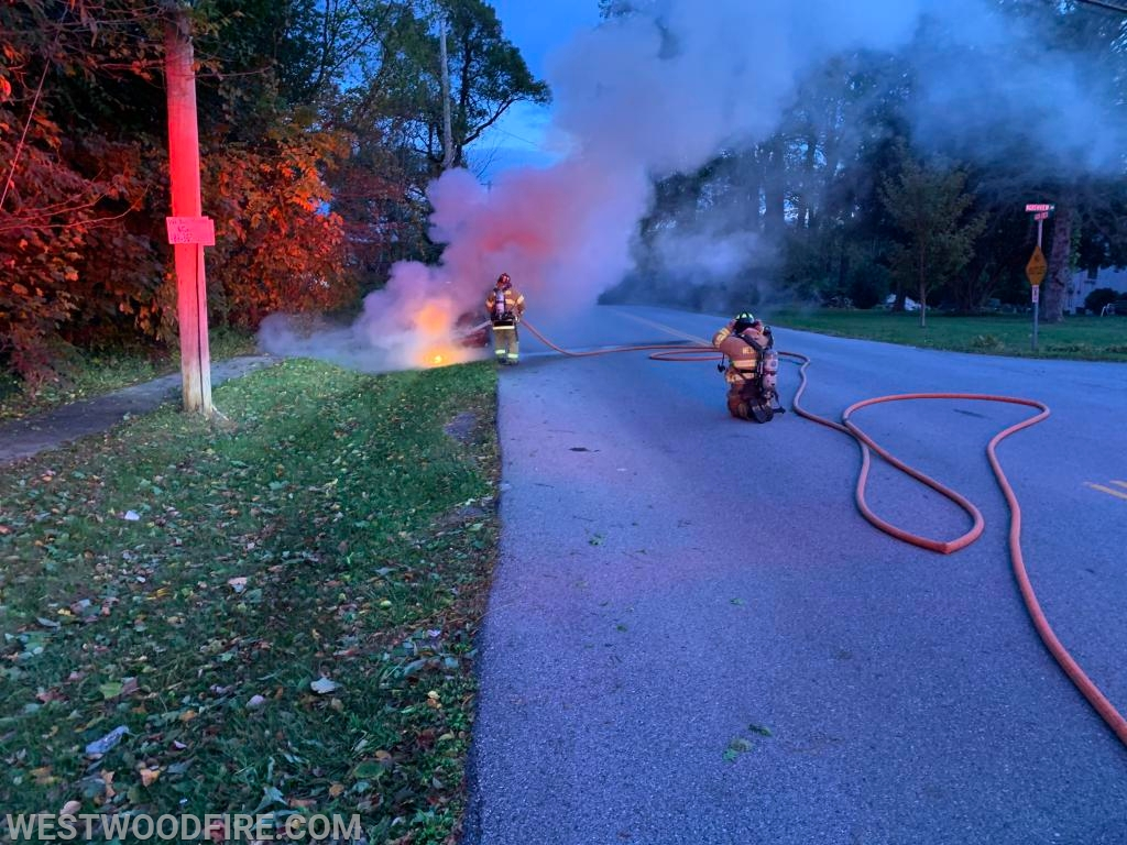 Firefighter/EMTs Grossman and Carro advance a hose line on the auto consumed by flames.
