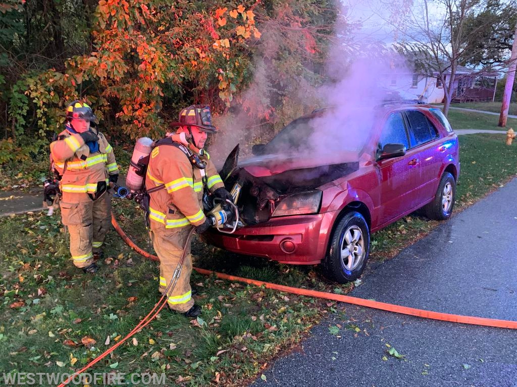 Firefighers use the hydraulic rescue tools to open the hood of the car.