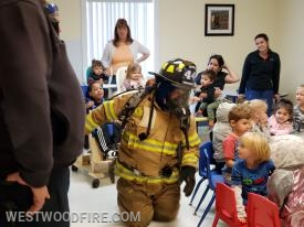 A Westwood firefighter shows the children when our gear is on, we are not anything to be scared of.