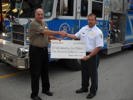 Chief Randy Scott accepting the $500.00 donation made to the Fire Division from the Store Manager Tom